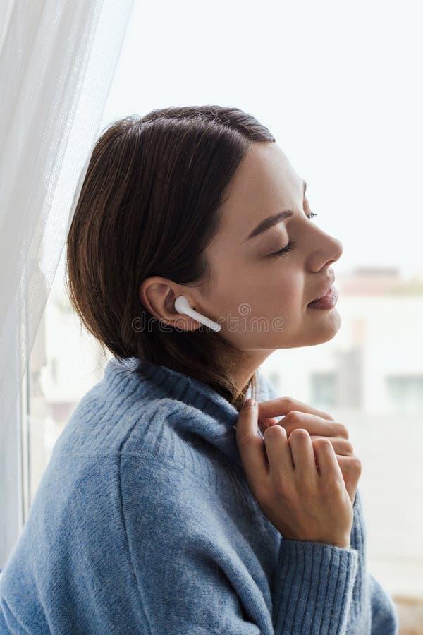 Dziewczyna w błękitnym pulowerze blisko okno z hełmofonami obraz royalty free