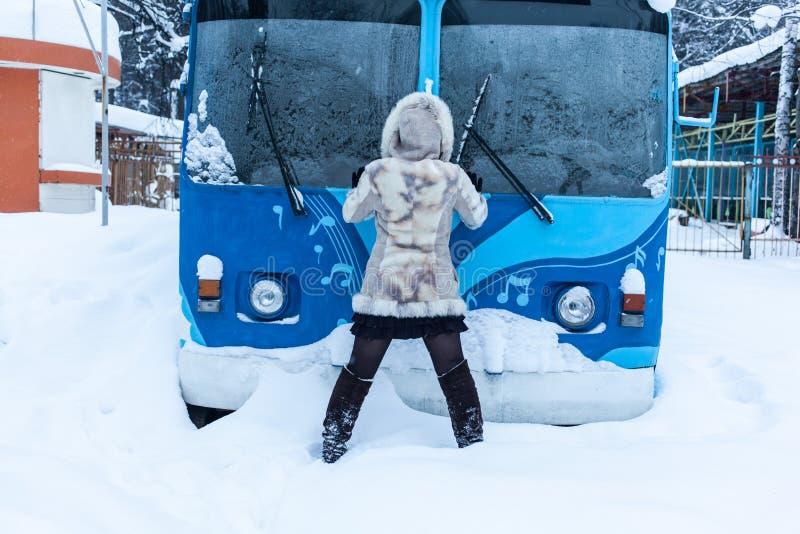 Dziewczyna w beżowego futerkowego żakieta i kapiszonu stojakach z jego z powrotem przed tramwaju autobusem zdjęcia royalty free