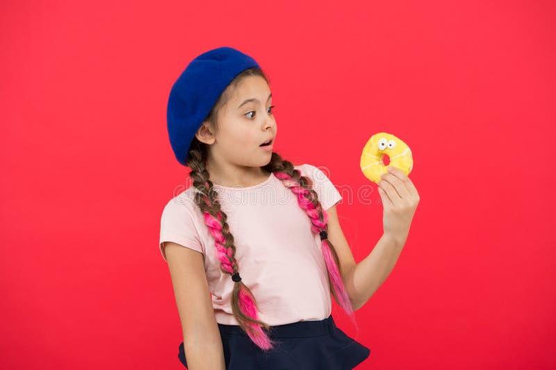 Dziewczyna w bereta chwyta pączka czerwieni kapeluszowym tle Dzieciak figlarnie dziewczyna je pączek Zdrowie i odżywiania pojęcie obrazy stock