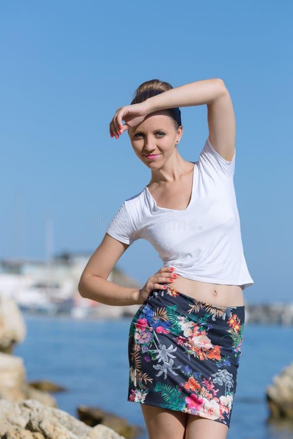 Dziewczyna w białej koszulce i krótkiej spódnicie pozuje przeciw morzu obraz royalty free