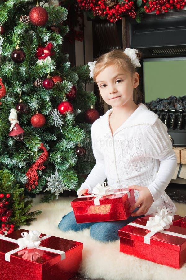 Dziewczyna w białej kurtce z prezentami zbliża choinki obrazy royalty free