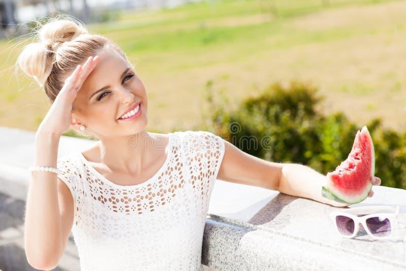 Dziewczyna w białej lato sukni je arbuza obrazy stock