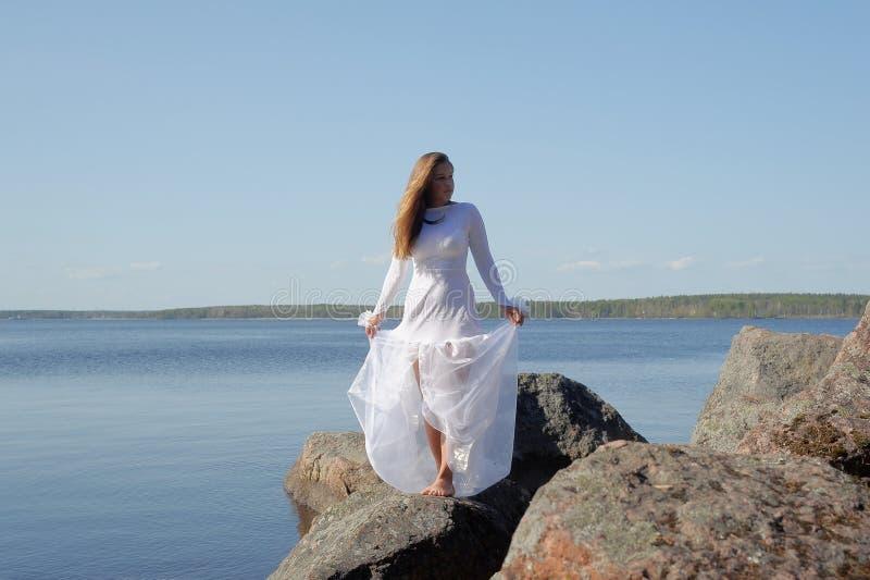 Dziewczyna w białej sukni przy jeziorem fotografia stock