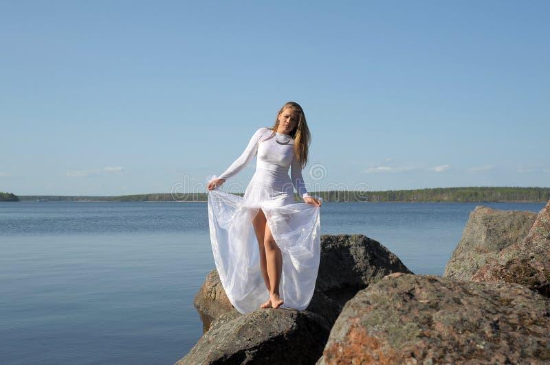 Dziewczyna w białej sukni przy jeziorem obrazy stock