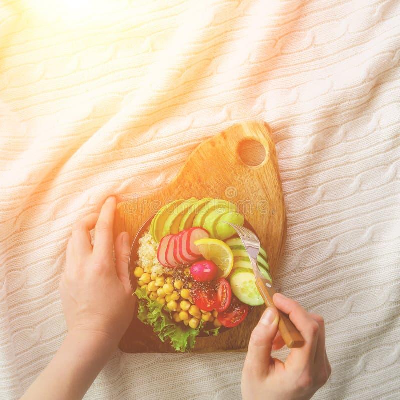Dziewczyna w białych cajgów chwytach w rękach rozwidla, weganinu śniadaniowy posiłek w pucharze z avocado, quinoa, ogórek, rzodki obraz royalty free