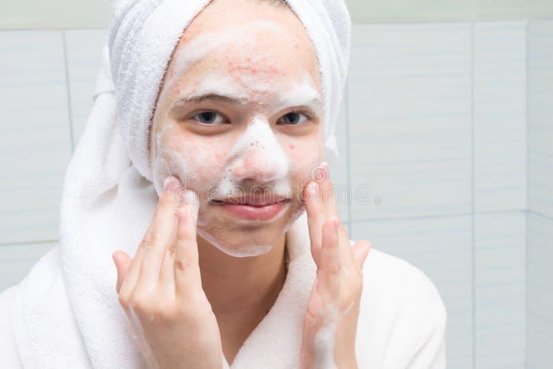 Dziewczyna w białym bathrobe w łazience mydli jej twarz z trądzik skórą zdjęcia stock