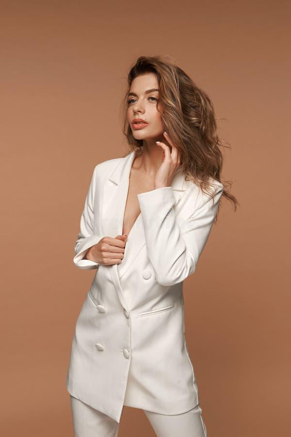 Dziewczyna w białym garniturze na beżowym tle obrazy royalty free