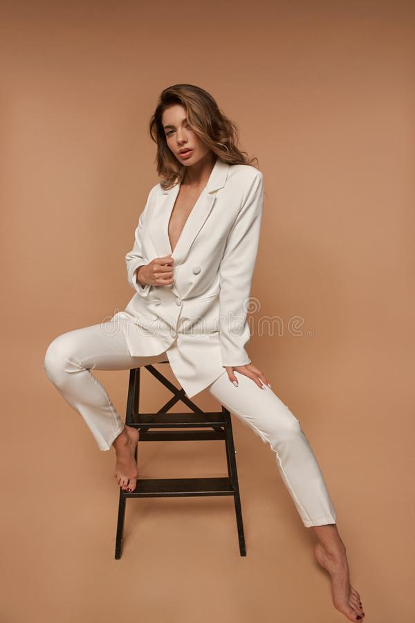 Dziewczyna w białym garniturze na beżowym tle fotografia royalty free