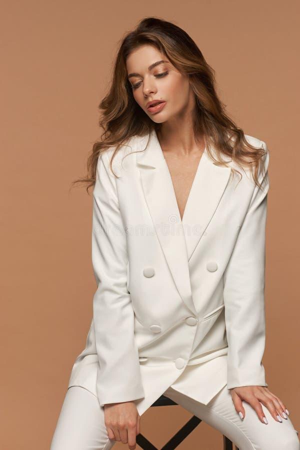 Dziewczyna w białym garniturze na beżowym tle obrazy stock