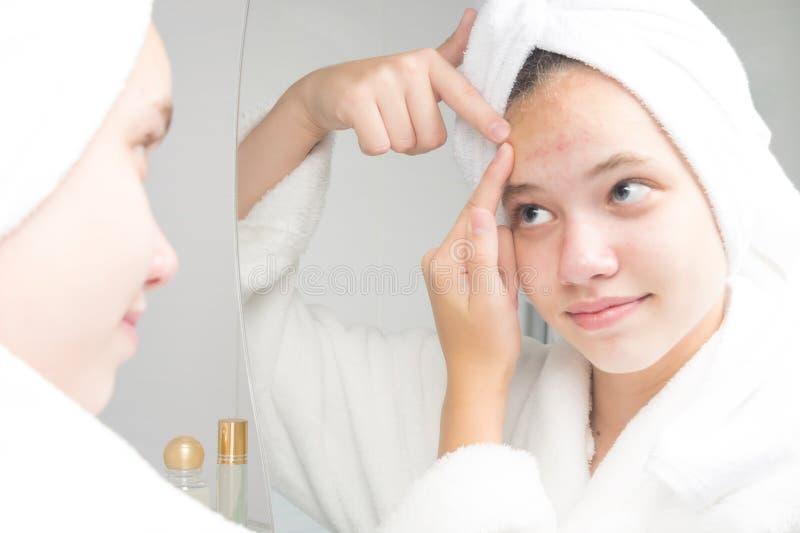 Dziewczyna w białym kontuszu gniesie trądzika na czole z jej rękami w łazience przed lustrem zdjęcia stock