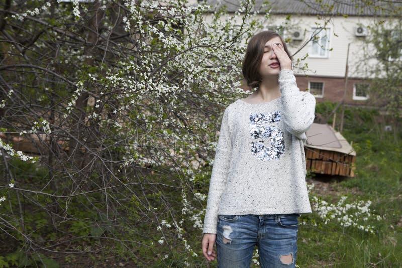 Dziewczyna w białym pulowerze dreamily zamyka ona blisko kwitnącej wiśni oczy od jaskrawego słońca w ogródzie fotografia stock