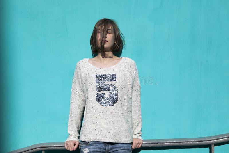 Dziewczyna w białym pulowerze dreamily zamyka ona oczy od jaskrawego słońca naprzeciw błękitnej ściany w przejściu podziemnym zdjęcie stock