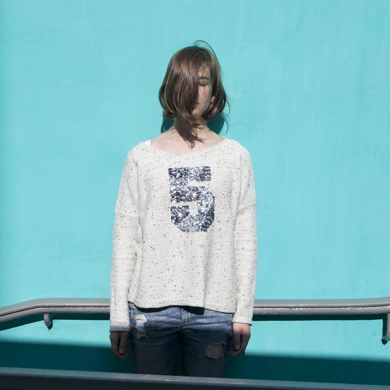 Dziewczyna w białym pulowerze dreamily zamyka ona oczy od jaskrawego słońca naprzeciw błękitnej ściany w przejściu podziemnym obrazy royalty free