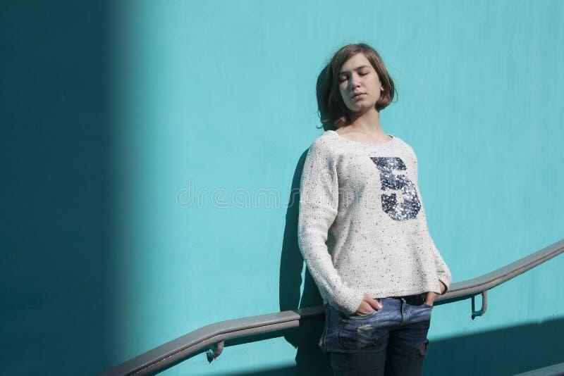 Dziewczyna w białym pulowerze dreamily zamyka ona oczy od jaskrawego słońca naprzeciw błękitnej ściany w przejściu podziemnym fotografia stock
