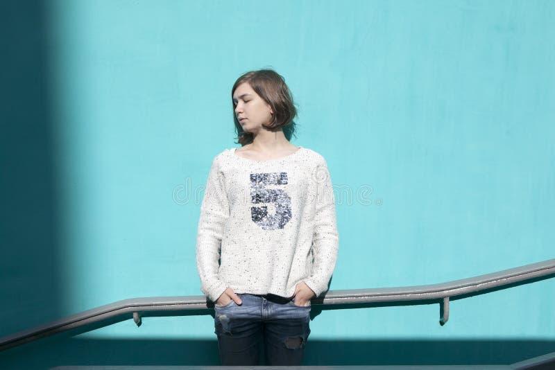 Dziewczyna w białym pulowerze dreamily zamyka ona oczy od jaskrawego słońca naprzeciw błękitnej ściany w przejściu podziemnym fotografia royalty free