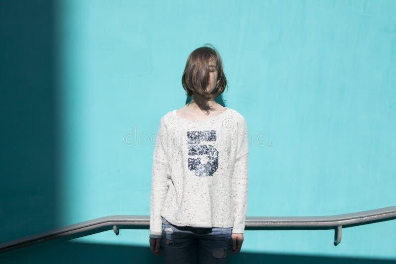 Dziewczyna w białym pulowerze dreamily zamyka ona oczy od jaskrawego słońca naprzeciw błękitnej ściany w przejściu podziemnym zdjęcia royalty free
