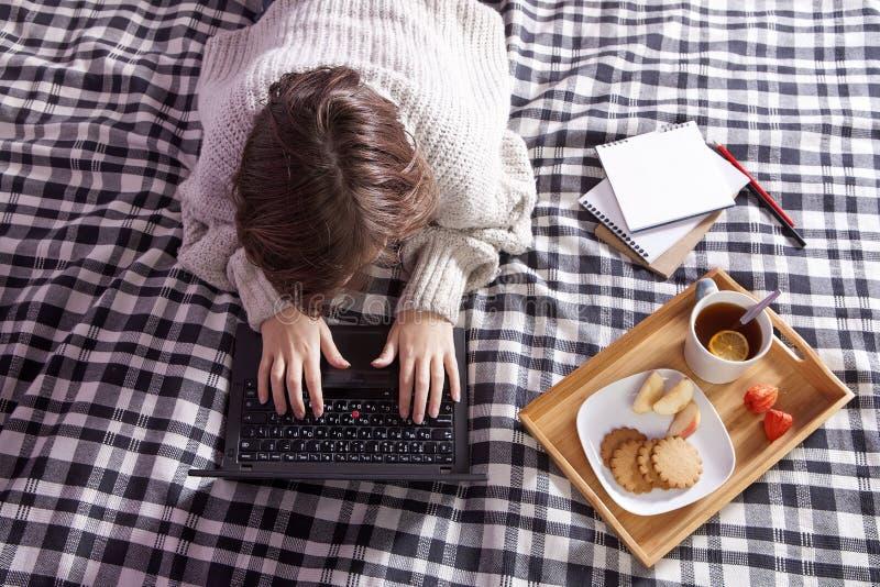 Dziewczyna w białym woolen pulowerze pracuje na laptopie taca z filiżanką herbata i talerz z imbirowymi ciastkami i jabłkiem na c zdjęcie stock