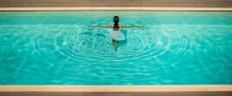 Dziewczyna w biel sukni w błękitne wody basenie na jasnym pogodnym popołudniu Kreatywnie obrazek zdjęcie stock