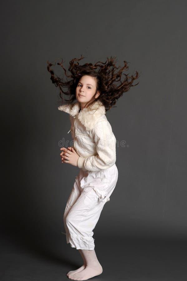 Dziewczyna w biel sukni doskakiwaniu zdjęcie stock