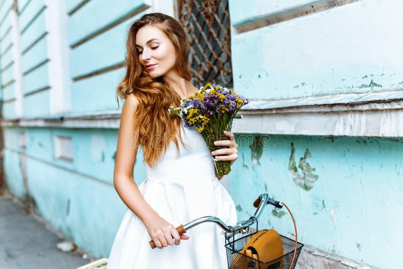 Dziewczyna w biel sukni z bicyklem i kwiatami blisko błękit ściany obraz royalty free