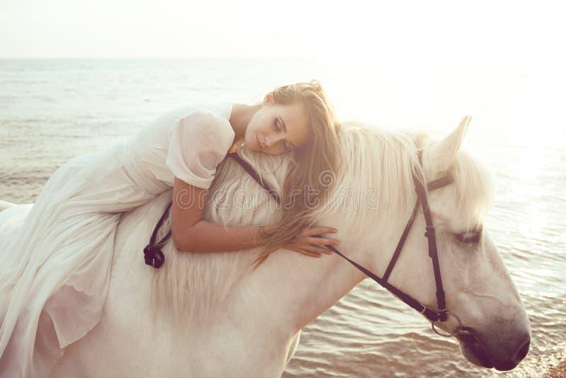 Dziewczyna w biel sukni z koniem na plaży zdjęcia royalty free