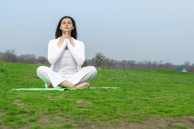 Dziewczyna w biel ubraniach robi joga ćwiczeniom zdjęcie stock