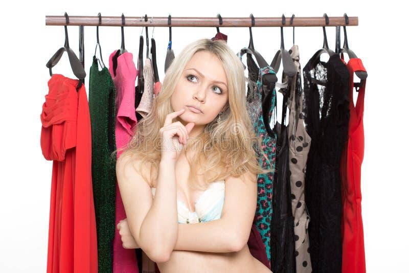 Dziewczyna w bieliźnie od odzieżowych wieszaków wybór suknia obrazy stock