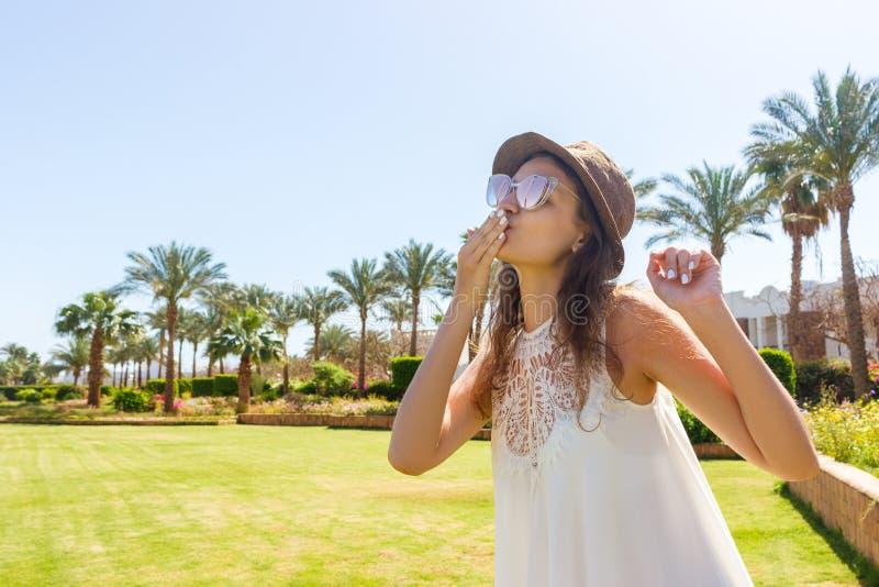 Dziewczyna w bielu wysyła lotniczego buziaka kamera długa suknia chodzi na tropikalnej palmie obraz stock