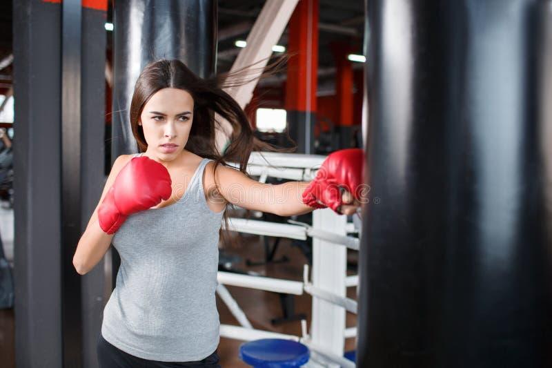 Dziewczyna w bokserskich rękawiczkach bije uderza pięścią torbę zdjęcia stock