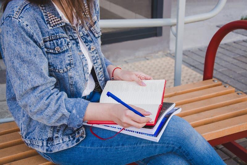 Dziewczyna w cajgów ubraniach siedzi na ławce, trzyma notatniki i pisze, Na ulicie, pisze w notatniku, studiuje w zdjęcie stock