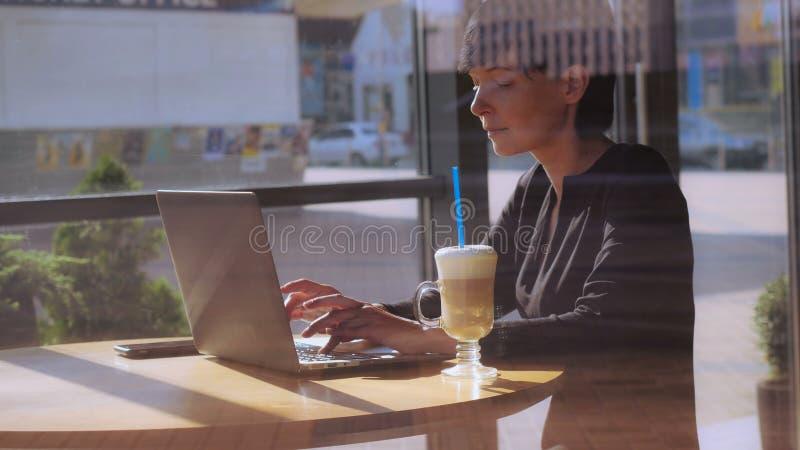 Dziewczyna w coffeehouse gawędzeniu w ogólnospołecznych środkach fotografia stock