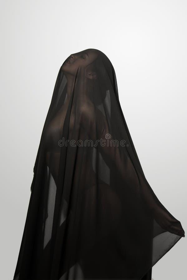 Dziewczyna w czarnej przejrzystej przesłonie na twarzy Konceptualny portret w studiu obrazy stock