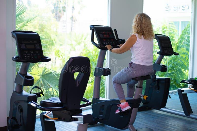 Dziewczyna w czarnej sport odzieży energicznie pracuje na ćwiczenie rowerze zdjęcia royalty free