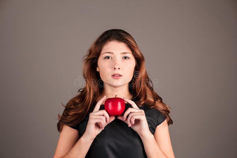 Dziewczyna w czarnej sukni z jabłkiem Tajemniczy wizerunek obraz royalty free