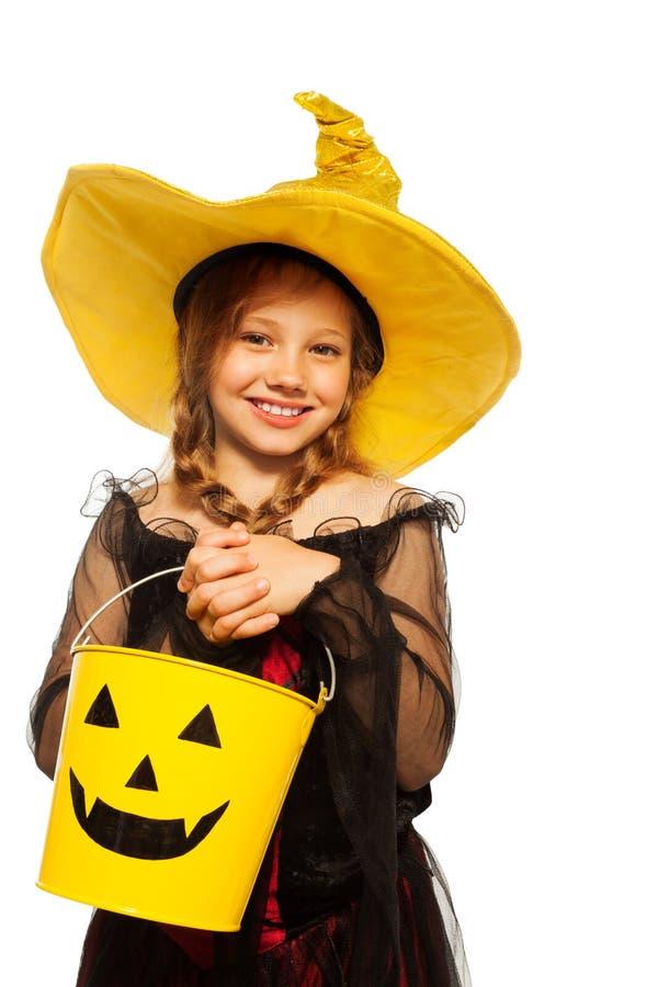 Dziewczyna w czarownica kostiumu i strasznym Halloweenowym wiadrze fotografia royalty free