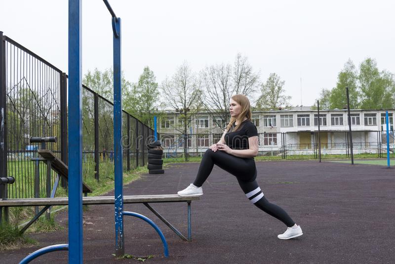 Dziewczyna w czerń sportów ubraniach angażował w sportach na boisku outdoors obraz stock