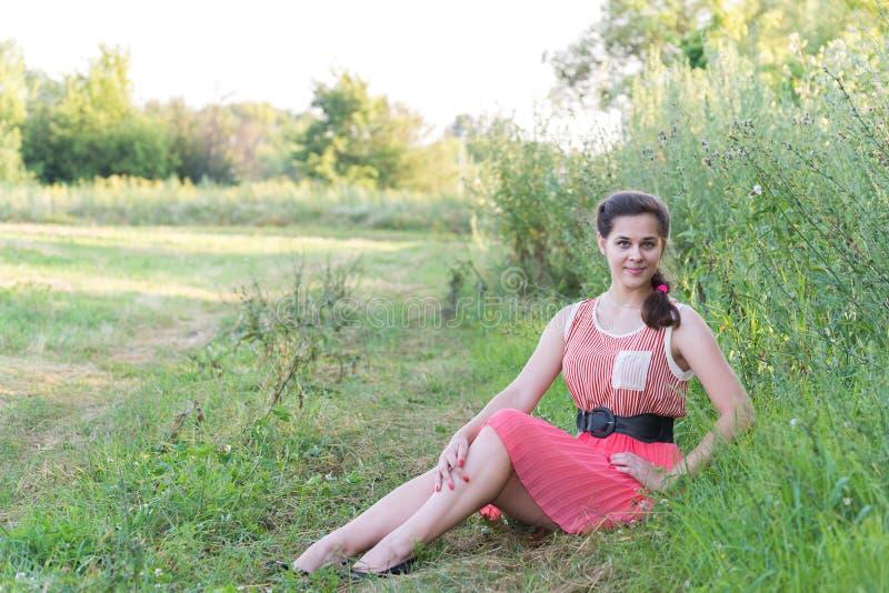 dziewczyna w czerwieni sukni siedzi na trawie obrazy stock