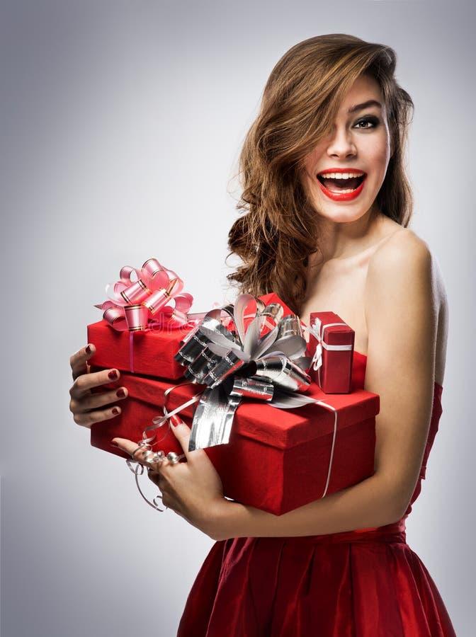 Dziewczyna w czerwieni sukni z prezentami zdjęcie royalty free