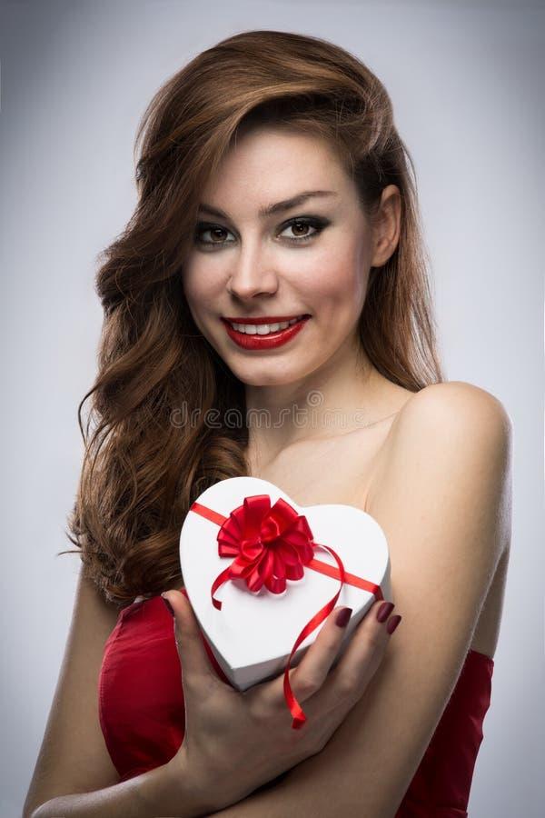 Dziewczyna w czerwieni sukni z prezentem obrazy royalty free