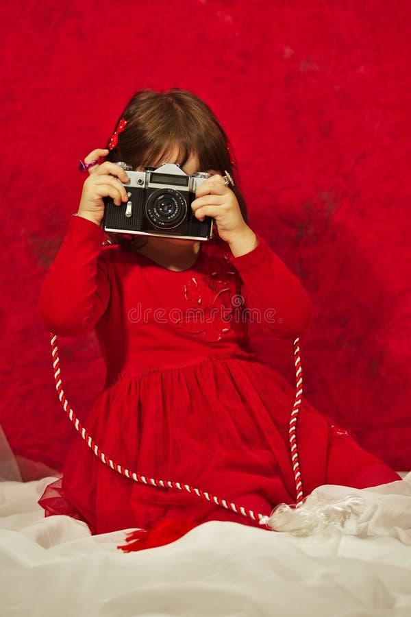 Dziewczyna w czerwieni używać rocznik fotografii kamerę zdjęcie stock