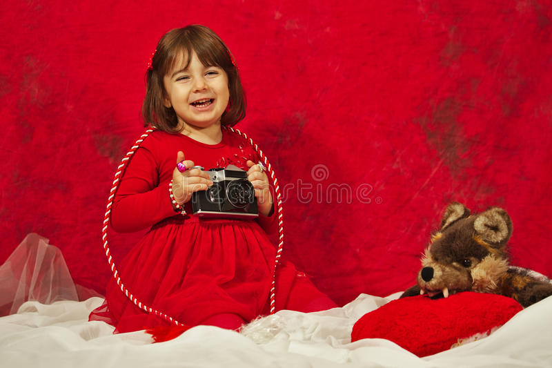 Dziewczyna w czerwieni używać rocznik fotografii kamerę obraz stock