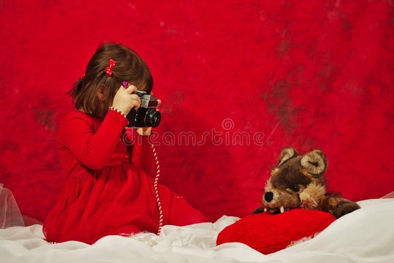 Dziewczyna w czerwieni używać rocznik fotografii kamerę fotografia stock