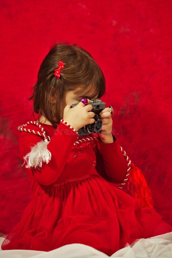 Dziewczyna w czerwieni używać rocznik fotografii kamerę zdjęcia stock