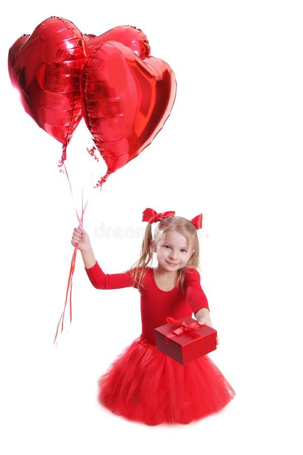 Dziewczyna w czerwieni z sercowatymi balonami i prezentem obrazy royalty free