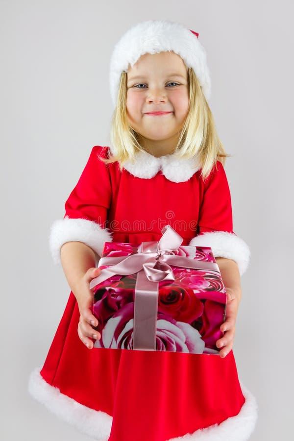 Dziewczyna w czerwonej nowy rok nakrętce z uroczystym prezentem zdjęcie stock
