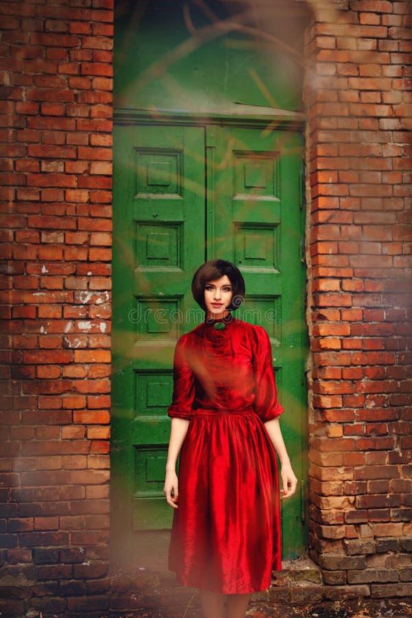 Dziewczyna w czerwonej retro sukni na tle rocznika drewniany drzwi obraz stock