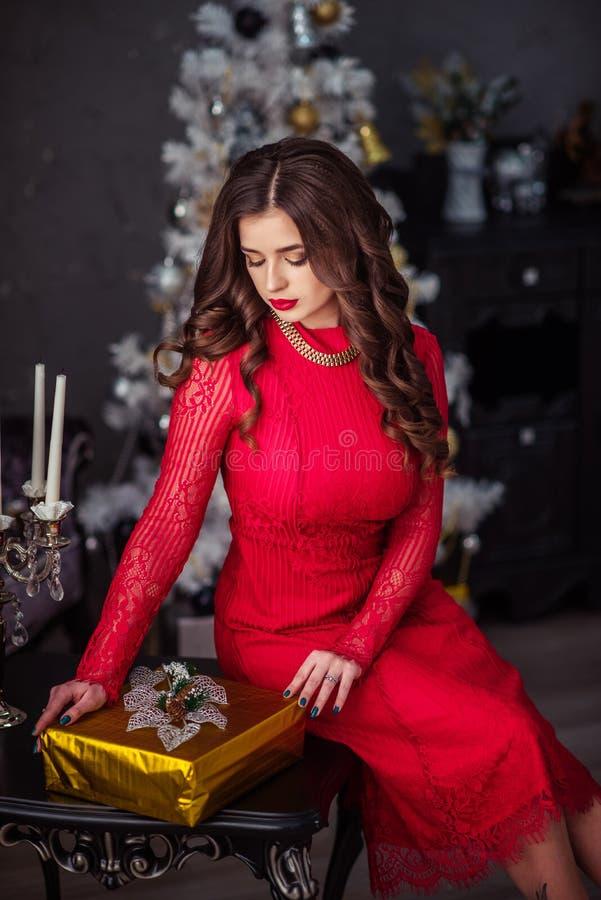 Dziewczyna w czerwonej sukni odpakowywa teraźniejszość zdjęcia royalty free