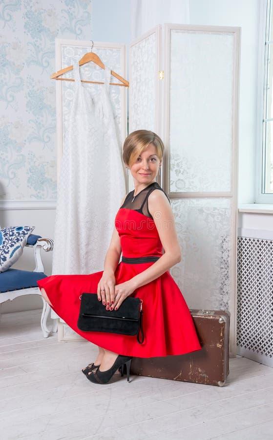 Dziewczyna w czerwonej sukni siedzi na walizce przed fol zdjęcie royalty free