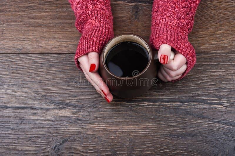 Dziewczyna w czerwonym pulowerze trzyma wielkiego kubek kawa rękojeścią fotografia stock