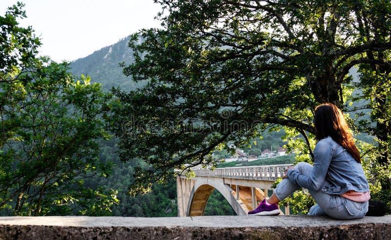 Dziewczyna w drelichu odzieżowym obsiadaniu na krawędzi ogrodzenia i spojrzeniach przy mosta Ä  urÄ ` eviÄ ‡ a fotografia stock
